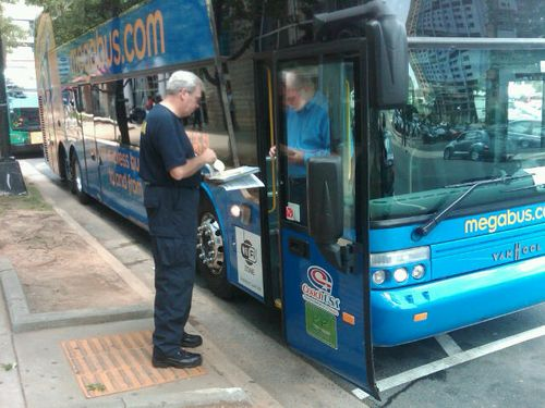Inspecting a curbside bus