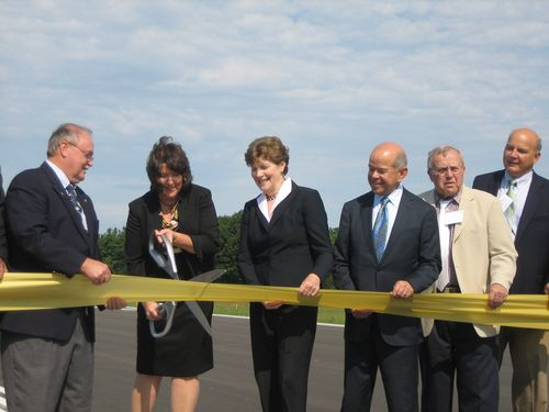 Mayor Lozeau cuts the ribbon as Senator Shaheen and Michael Huerta (to her right) look on