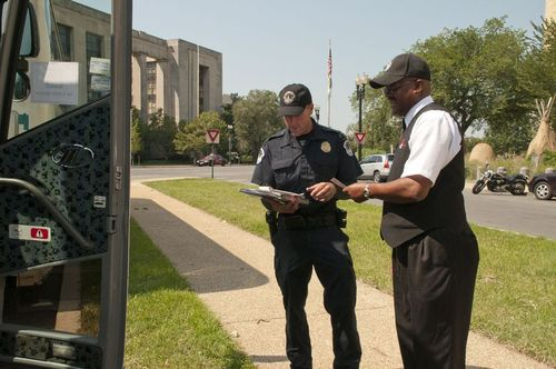 Photo of a strike force inspector checking a driver's hours-of-service.