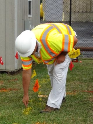Photo of utility employee painting warning marks near a gas line