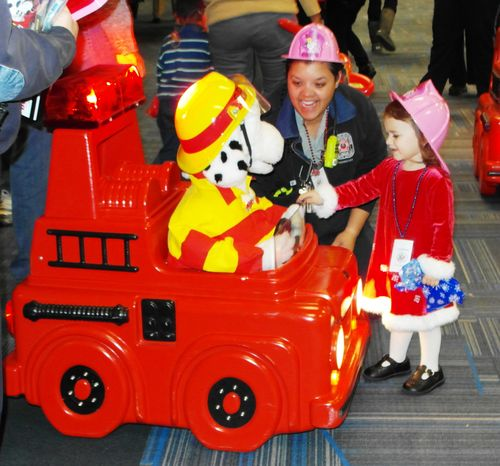 Photo of a girl greeting a toy dog in a firetruck