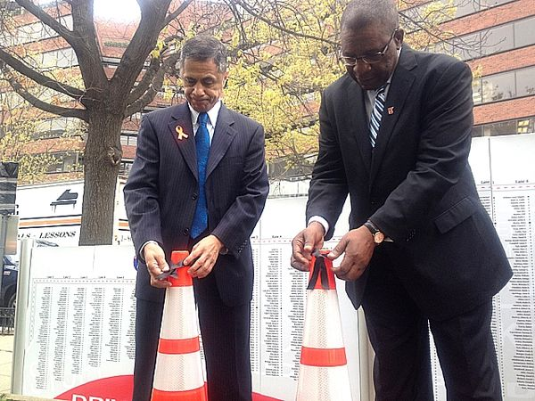 Victor Mendez applies ribbons to work zone cone