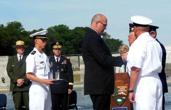 Deputy Maritime Administrator Jaenichen putting medals on Van Splunder